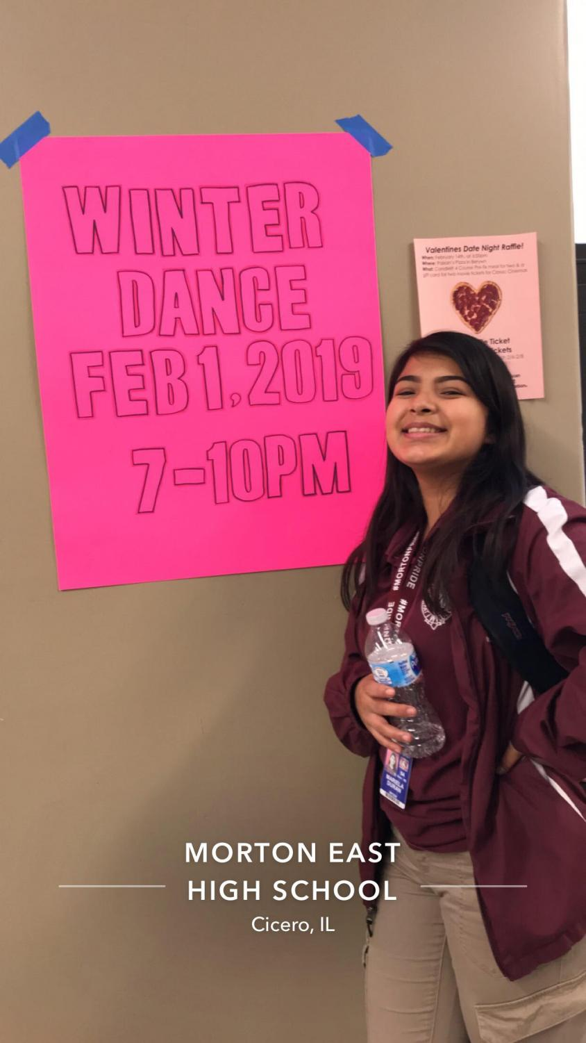 Mariela Duran  posing infront of a winter formal poster
