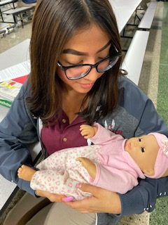Senior, Lizbeth Mozo holds her baby.