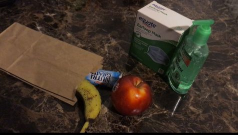 Image of food alongside a box of masks and hand sanitizer. Students can pick up food at Morton East. Testing locations require the use of a mask and will provide hand sanitizer.