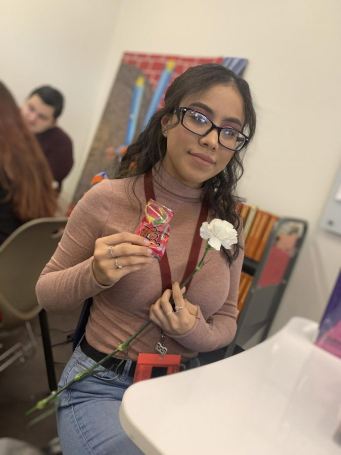 Senior Evelyn Rosales receiving a carnation and a Ringpop