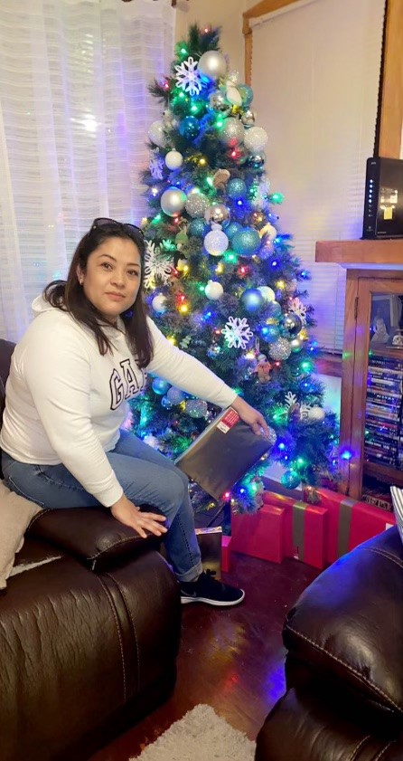 Cicero resident Katie Gonzalez places her final Christmas present for her family under her Christmas Tree. After a stressful time doing her holiday shopping, she happily discovered what she believed to be the best gifts for her loved ones.